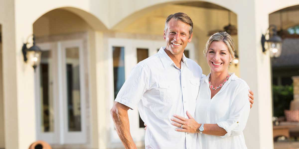 Smiling couple in front of house